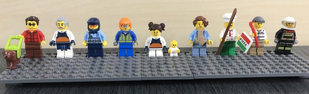 Acht große LEGO Minifiguren, ein Kind und ein Baby