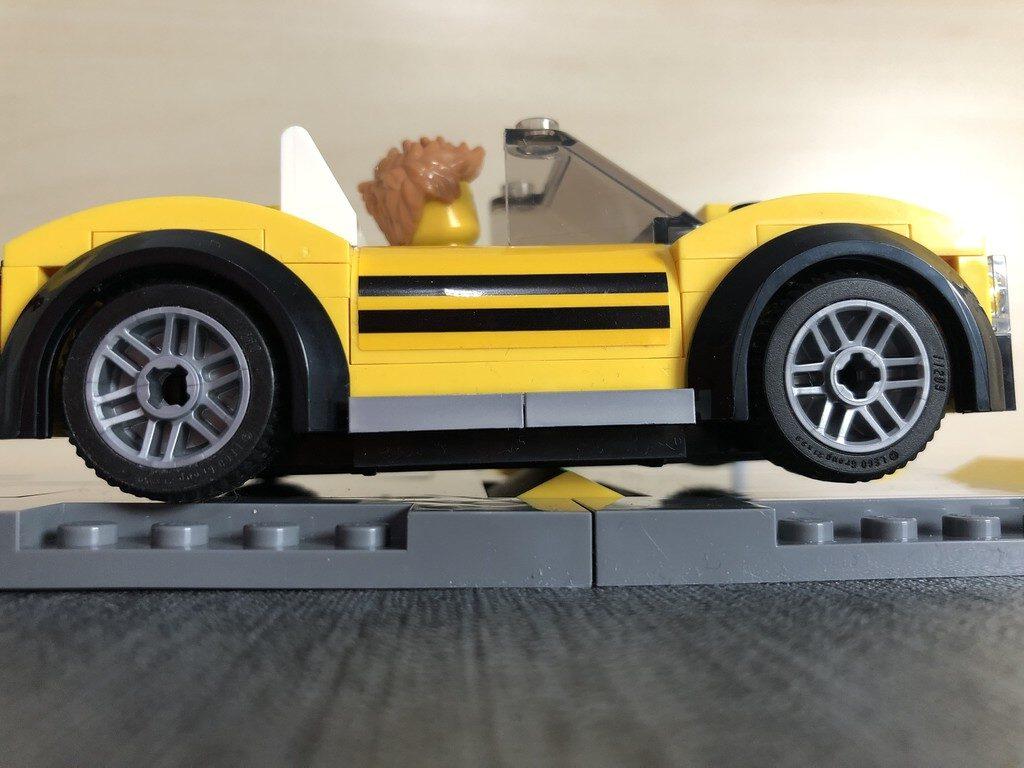 Gelbes LEGO Fahrzeug ist zu tief für Bremsschwelle und berührt diese mit der Karosserie